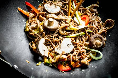 Hot Asian soba noodles with vegetables, mushrooms and sauce. On rustic background Imagens - 124763707