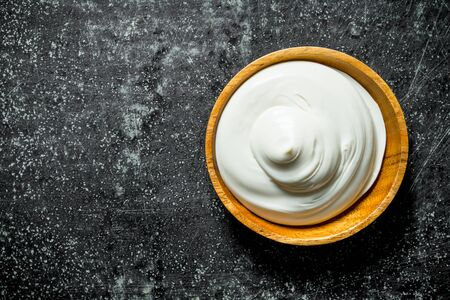 Mayonnaise in a wooden plate. On dark rustic background Banque d'images - 124763710