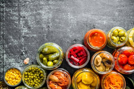 Preserved food in glass jars. On dark rustic background Stok Fotoğraf