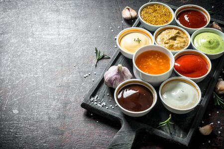 A variety of delicious sauces with slices of garlic. On dark rustic background