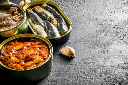 Open tin cans with canned fish and meat. On black rustic background