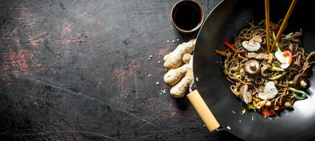 Fragrant soba noodles in a wok pan with mushrooms and fresh vegetables. On dark rustic background