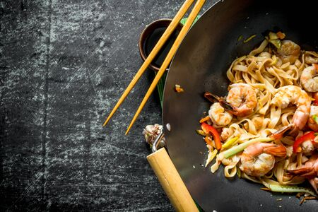 Chinese wok. Udon noodles in a wok pan with shrimp and sauce. On dark rustic background Banque d'images - 124763650