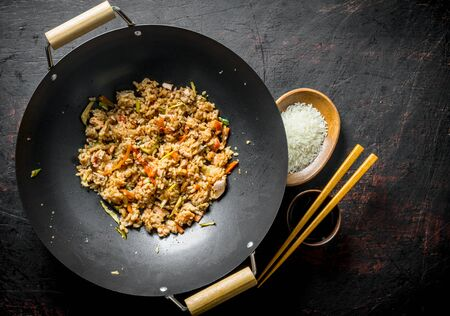 Chinese wok. Cooked rice in a wok pan and uncooked rice on a plate. On dark rustic background