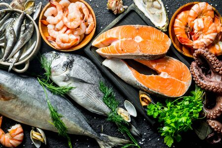 Fresh salmon steak with a variety of seafood and herbs. On black rustic background Stok Fotoğraf