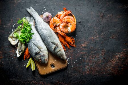 Fresh fish on a cutting Board with oysters, shrimp and crayfish. On dark rustic background