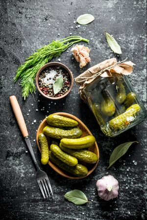 Pickled homemade cucumbers with dill and garlic. On dark rustic background