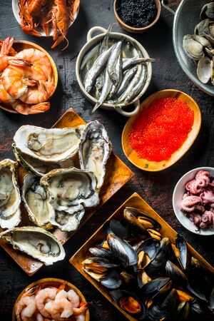Fresh seafood on various plates. On dark rustic background Stok Fotoğraf - 124763618
