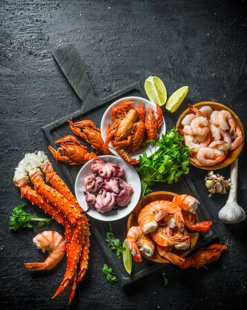 Various seafood on a cutting Board with garlic, lime and parsley. On black rustic background Фото со стока
