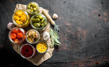 Pickled vegetables in jars on the paper with the Bay leaves and the cloves of garlic. On dark rustic background Фото со стока