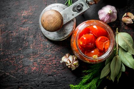 Pickled tomatoes in a glass jar with garlic, spices and Bay leaf. On dark rustic background Banque d'images - 124763625