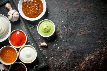 Set of different types of sauces. On dark rustic background