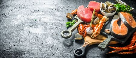 Tuna and salmon steaks on cutting boards. On black rustic background
