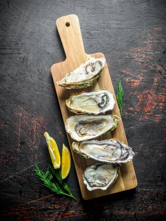 Opened raw oysters on a wooden cutting Board with lemon and dill. On dark rustic background