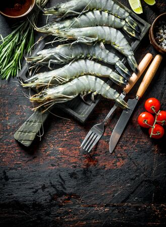 Raw shrimps uncooked with tomatoes and rosemary. On dark rustic background Stock Photo