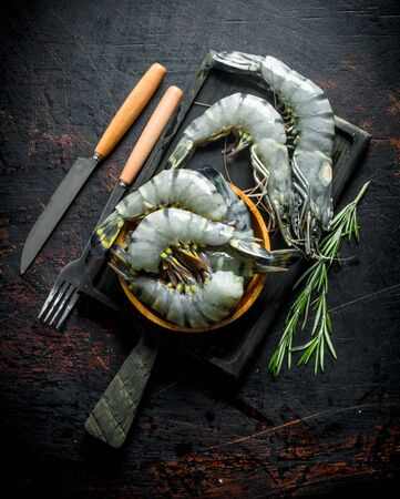 Raw shrimps on a cutting Board with sprigs of rosemary. On dark rustic background Stok Fotoğraf - 124763539