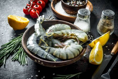 Whole shrimps raw on a plate with spices, tomatoes and lemon. On dark rustic background Stock Photo