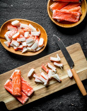Sliced crab sticks on a cutting Board with a knife. On black rustic background Stok Fotoğraf - 124763548