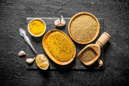 Different types of mustard on a stone Board with garlic. On black rustic background