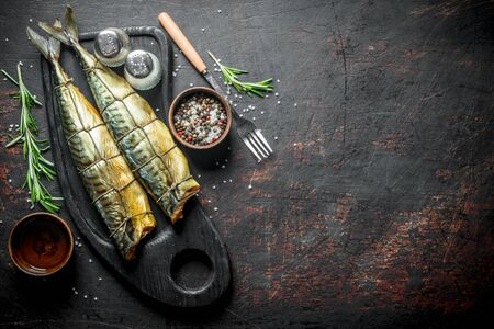 Smoked mackerel with spices and rosemary. On dark rustic background