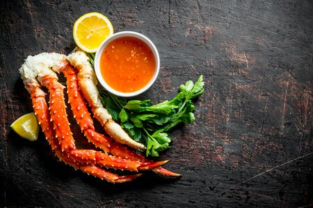 Fresh crab with lemon slices, parsley and sauce. On dark rustic background Stok Fotoğraf - 124763461