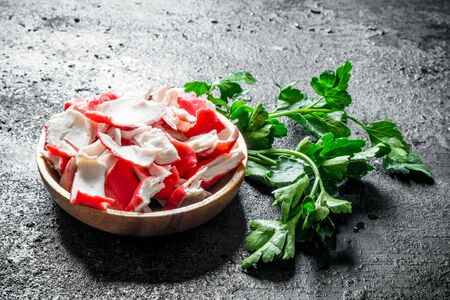 Crab meat on a plate of parsley. On black rustic background Stok Fotoğraf - 124763465