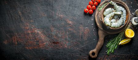 Raw shrimps in a plate on a cutting Board with cherry tomatoes, rosemary and cut lemon. On dark rustic background Stok Fotoğraf - 124763467