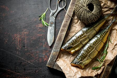 Smoked mackerel on a wooden tray with old twine. On dark rustic background
