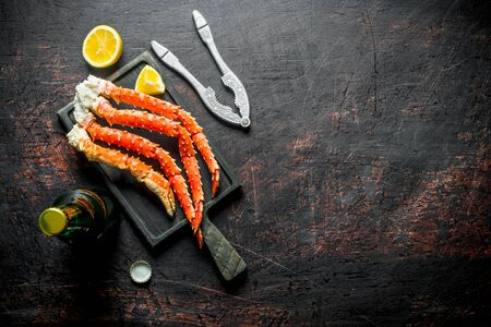 Crab on a cutting Board with a bottle of beer and slices of lemon. On dark rustic background Stok Fotoğraf - 124763471