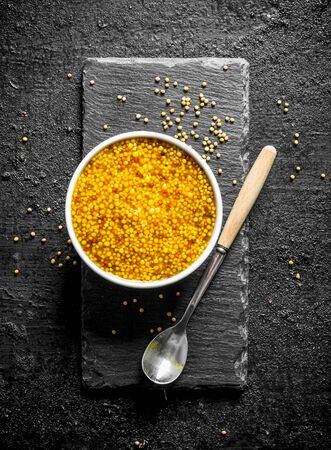 Dijon mustard in the bowl. On black rustic background Banco de Imagens