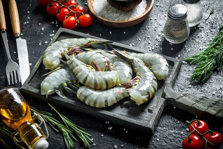 Fresh whole uncooked shrimps with rosemary and tomatoes. On black rustic background