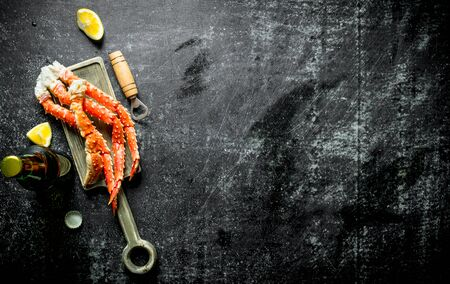 Crab on a cutting Board with beer and lemon slices. On dark rustic background Stok Fotoğraf - 124763403