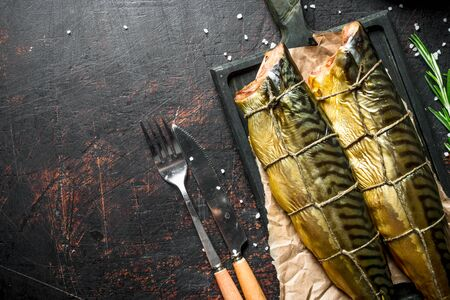 Fragrant smoked fish mackerel on a cutting Board. On dark rustic background
