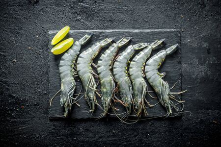 Fresh raw shrimps on a stone Board with lime slices. On black rustic background Stok Fotoğraf - 124763408