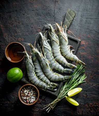 Raw shrimps on a cutting Board with lime, rosemary and spices. On dark rustic background Stok Fotoğraf