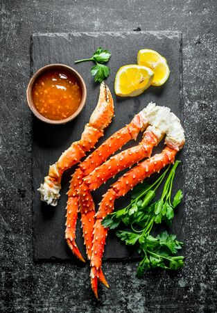 Crab on a stone Board with sauce, parsley and lemon slices. On dark rustic background Stok Fotoğraf - 124763415
