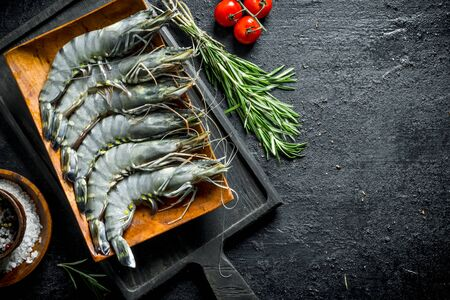 Raw shrimps in a plate on a cutting Board with rosemary, tomatoes and spices. On black rustic background Stok Fotoğraf - 124763420