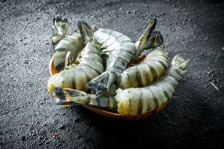 Fresh tiger shrimps on a plate. On black rustic background Stok Fotoğraf