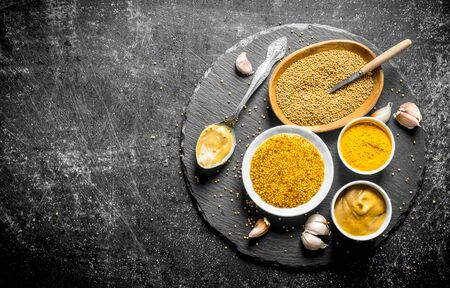 Different types of mustard on a stone Board with garlic. On dark rustic background Фото со стока