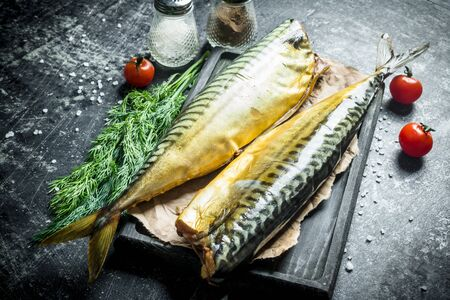 Whole smoked mackerel on a cutting Board with greens, tomatoes and spices. On dark rustic background Banco de Imagens