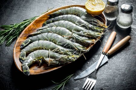 Fresh raw shrimps with rosemary. On dark rustic background