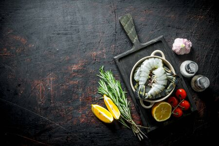 Raw shrimps not cooked with tomatoes, lemon slices and rosemary. On dark rustic background Stok Fotoğraf - 124763366