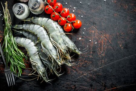 Raw shrimps with rosemary, tomatoes and spices. On dark rustic background Stok Fotoğraf - 124763367