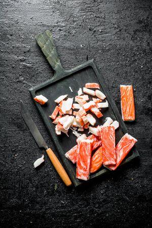 Sliced crab sticks on a cutting Board. On black rustic background Stok Fotoğraf - 124763370