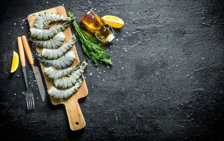 Uncooked raw shrimps on a wooden cutting Board. On black rustic background
