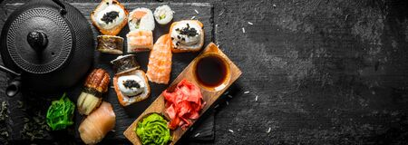 Traditional Japanese sushi rolls with green tea. On black rustic background