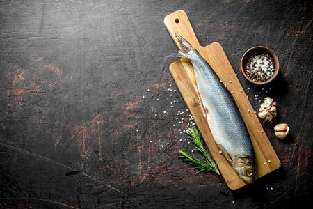 Salted herring with spices, rosemary and garlic cloves. On dark rustic background