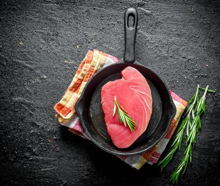 Piece of raw tuna in a pan with rosemary. On black rustic background
