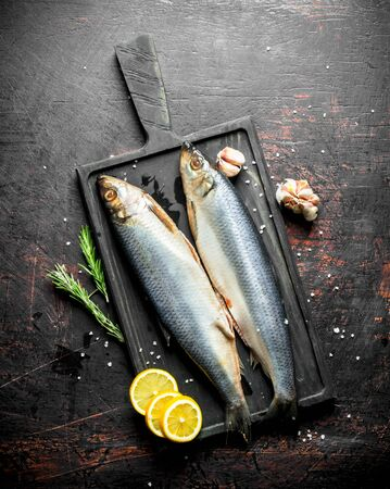 Salted herring on a cutting Board with lemon, garlic cloves and rosemary. On dark rustic background Stok Fotoğraf