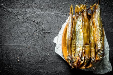 Smoked fish on paper. On black rustic background Banco de Imagens